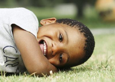 PATRIZIA Child Care Grabouw, Südafrika - Junge im Gras lacht