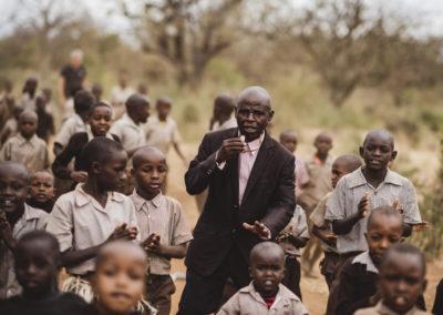 PATRIZIA School Syangeni, Kenia - Mann mit Pfeiffe Kinder klatschen