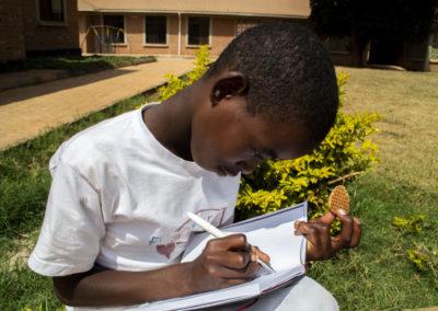 PATRIZIA Child Care Songea, Tansania - Kind schreibt in Buch