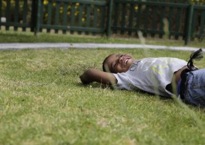 PATRIZIA Child Care Grabouw, Südafrika - Kind liegt im Gras