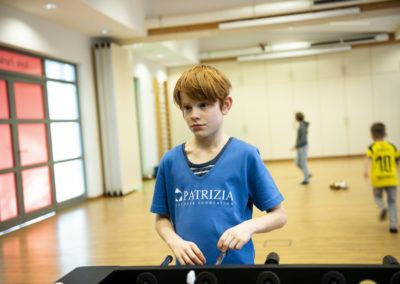 PATRIZIA Aftercare Hamburg, Deutschland - Junge spielt Kicker mit PCF Tshirt