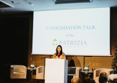 Event 1. PATRIZIA Foundation Talk Frankfurt - Her Majesty Queen Mother Sangay Choden Wangchuck am Pult über PATRIZIA Childcare Bumtang, Bhutan